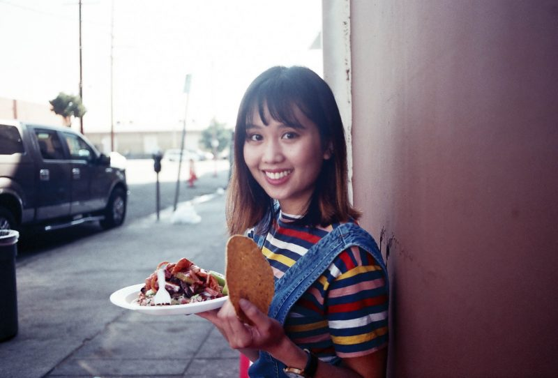 Girl Eating Mariscos Jalisco Taco Truck in Los Angeles